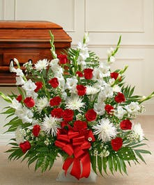 A Sympathy Basket fearturing a Mix of Red & White Flowers.