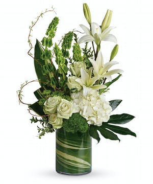 The Botanical Beauty Bouquet feauturing white lilies, white hydrangea, bells of Ireland in a leaf wrapped vase