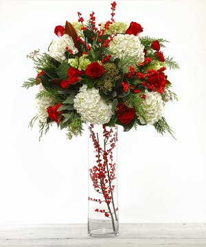 Christmas Party Buffet Arrangement by Carithers Flowers Atlanta featuring hydrangea, roses, ilex berries and holiday greens.