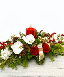 The Christmas Traditions Table Centerpiece Premium   Holiday floral greens, pillar candle, white stock roses and orchids