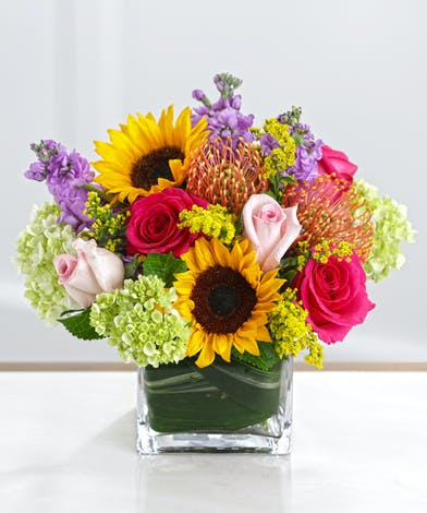 The Countryside Garden Bouquet features Sunflowers, Lilies, Roses, and Hot Pink Gerbera Daisies