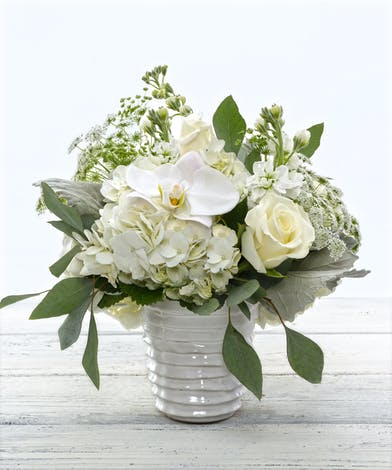 Gorgeous white hydrangea, stock, ivory roses, and exotic orchids in a keepsake decor container