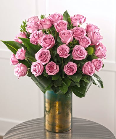 Deliver three dozen purple roses in a gorgeous home decor vase.