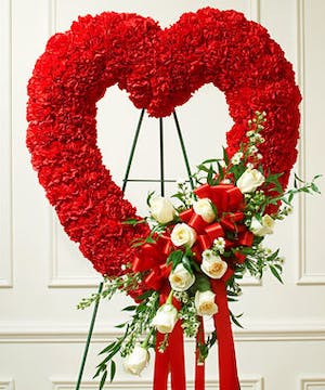 A red open heart with a sash of white roses