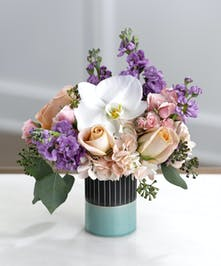 The Petite Pastel features garden hydrangea, English roses, lavender stock and orchids.