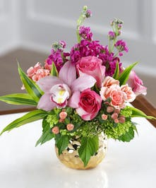 Peachy Keen Bouquet features stock, hydrangea, peach roses, orchids and hypericum berries in a keepsake gold decor vase