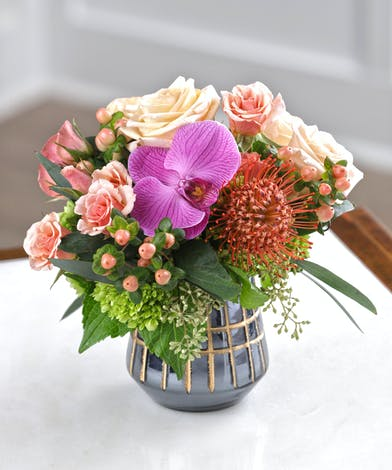 The Peachtree Petite features hydrangea, peach roses, pincushion protea, hypericum and purple orchids in a decor container.
