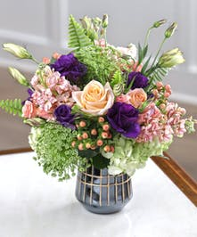 The Peachtree Bouquet features Tiffany peach roses, peach stock, purple lisianthus and garden hydrangea.