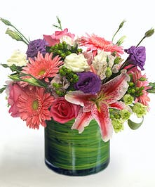 The Princess Bouquet features pink gerbera daisies, lilies, roses, and lisianthus in a glass cylinder.