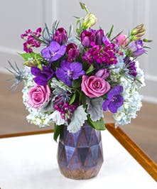 The Fields of Lavender arrangement features hydrangea, purple roses, purple lisianthus, stock, and thistle in a decor vase.