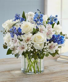 White roses, blue delphinium and holiday greens