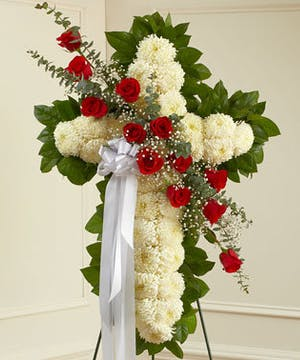 A White Standing Cross with a Red Floral Sash