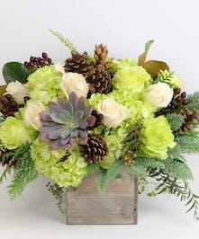 The Winter Spirit arrangement featuring hydrangea and greens in a wooden florist box.