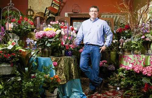 Surrounded by flowers and plants alike, Charles Carithers poses in his showroom