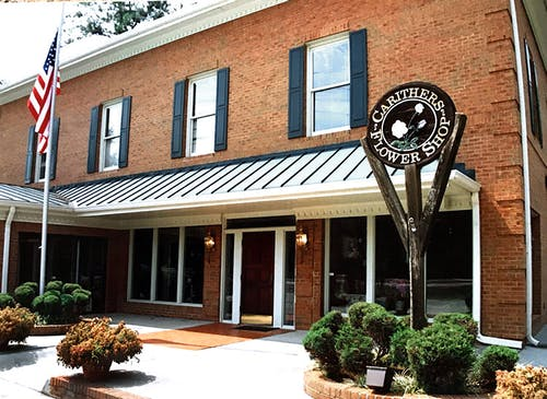 An exterior view of our Marietta location, featuring our wooden sign and an American flag